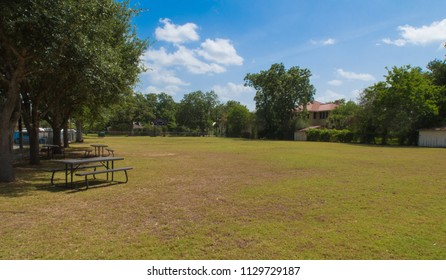 an empty playing field bordered by trees