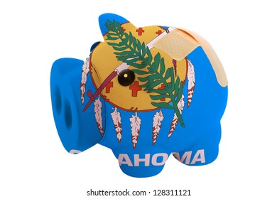 empty poor man piggy rich bank in colors flag of us state of oklahoma on white