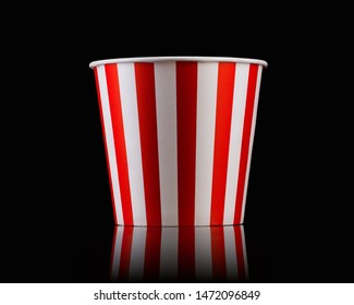 Empty popcorn striped bucket isolated on black background, concept of watching TV or cinema.