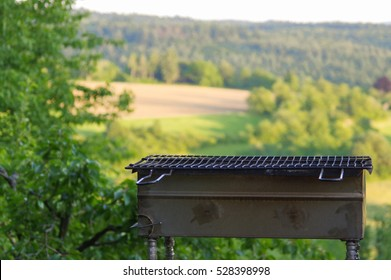 a empty portable BBQ grill in front of a fresh green summer landscape