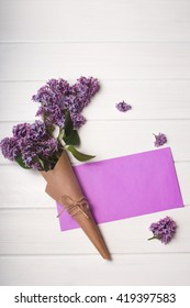 Empty postal envelope and bouquet of lilac flowers on the white wooden background, copy space. Top view.