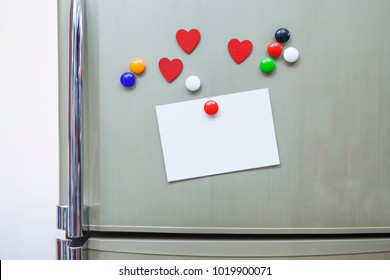 empty postcard stick  with multi color and red heart  magnet on  refrigerator door for reminder