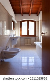 Empty private bathroom in a home. The bathroom is composed of a toilet, a sink, a bathtub and a bidet. It also has a window. We can see the ceiling with wooden beams
