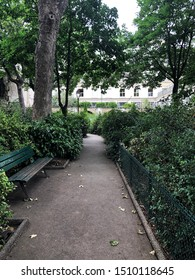 Empty private bench at Paris France. Green trees and bushes surrounded bench.