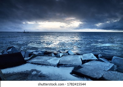 Empty promenade and snow-covered breakwaters close-up. Lighthouse in the background. Baltic sea, Latvia. Dark storm clouds. Winter, seasons, climate change, global warming concepts. Long exposure