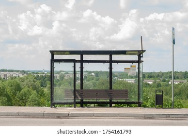 Empty public transport stop in summer. Self-isolation. Bus and minibus stops. Glass stop with a bench and a trash can. Stop without people, without passengers. bus stop sign