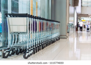 empty pushcart in airport. people walking on background