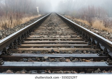 Empty railroad track going into a fog, outdoor landscape. Perspective view