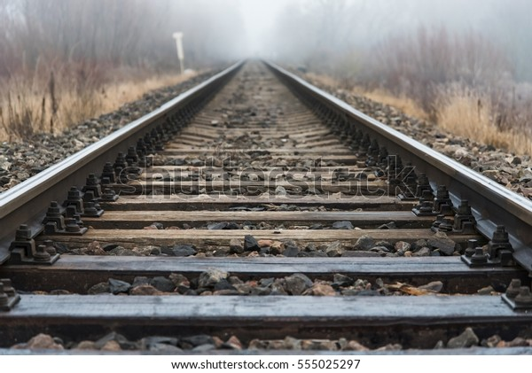 Empty Railroad Track Going Into Fog - Stock Photo