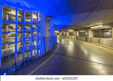 Empty ramp in circular underground parking garage with colorful lighting under an international airport