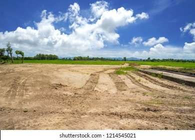 Empty reclamation area, vacant compact soil of construction site with car tire printed and beautiful landscape view and blue sky. Land plot for sales and real estate development sale project concept