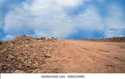 Empty reclamation and compact land and dump truck carrying red soil on construction site with blue sky. Land plot for sales and real estate development project concept background.