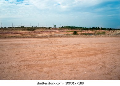 Empty reclamation, compact land and lake or water reservoir, red soil on construction site with blue sky. Land plot for sales and real estate development project concept background