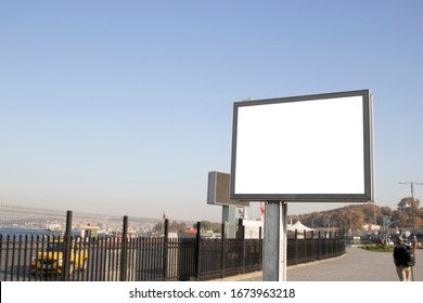 Empty rectangular bilboard. Photographed on the edge. Walking people.