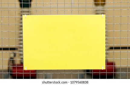 Empty rectangular yellow blank on a mesh fence.