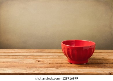 Empty red bowl on wooden vintage table over grunge background