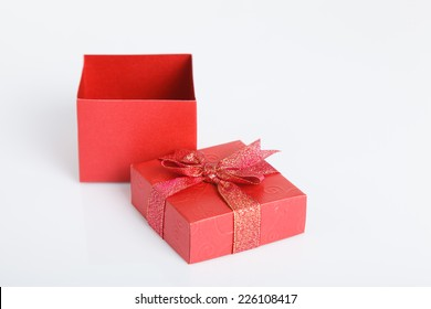 An empty red gift box with the lid off on white background