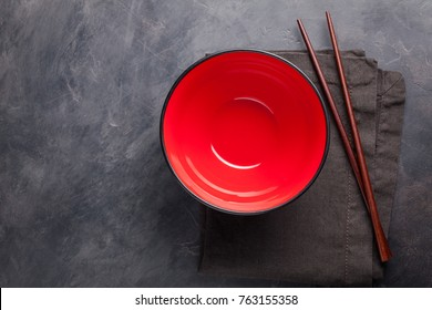 Empty red glass bowl of Chinese noodles and wooden sticks on dark concrete background. Top view with copy space. Flat lay.