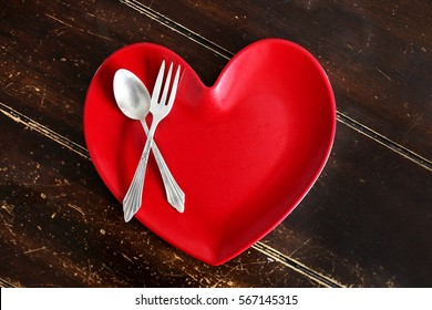 An empty red heart shaped dinner plate with a silver spoon and fork is sitting on an old worn out wood planked table.