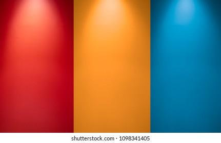 Empty red, orange or yellow and blue wall with spotlights. Illuminated lamp light. Room  interior with ceiling lamp light and colorful wall. Studio wall texture background