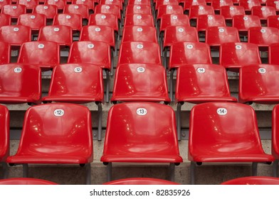 Empty red plastic seats in a stadium.