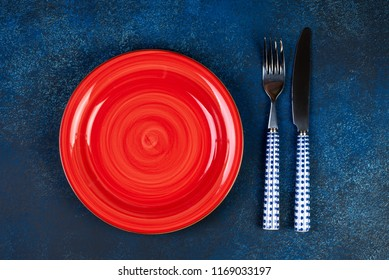 Empty red plate, fork, knife, spoon on blue background, top view