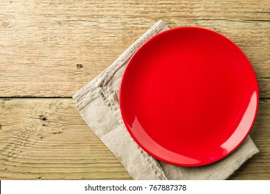 An empty red plate on a rustic wooden table top background