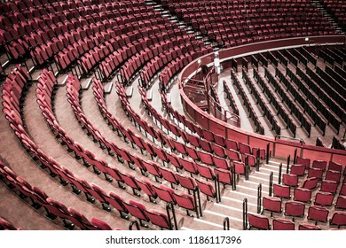 Empty red seats in large theatre setting with no people