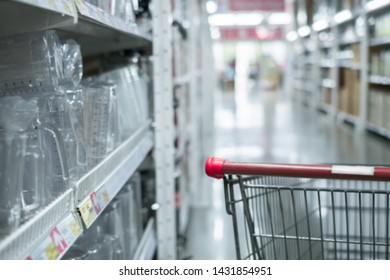 Empty red shopping cart .Abstrat blure supermarket retail and shopping mall interior for background.