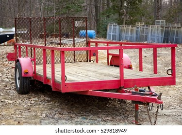 Empty red trailer at wooded construction site. Horizontal.