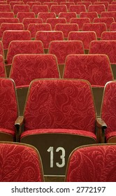 empty red wooden cinema/theater seats, number 13 in the middle,