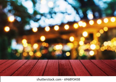empty red wooden floor or wooden terrace with abstract night light bokeh of night festival in garden, blurred background, copy space for display of product or object presentation, vintage color tone