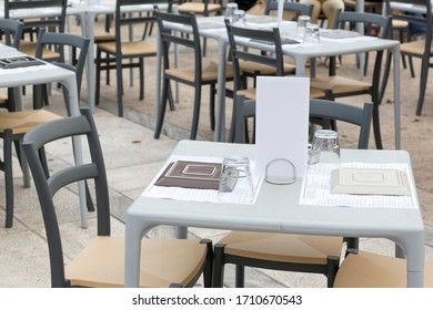 Empty restaurant terrace with simple setted tables.