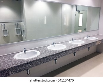 Empty restroom public men bathroom interior with washing hand sinks. Mirror with hand basin in clean toilet.
