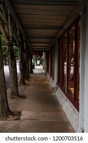 Empty retail storefront covered sidewalk with trees