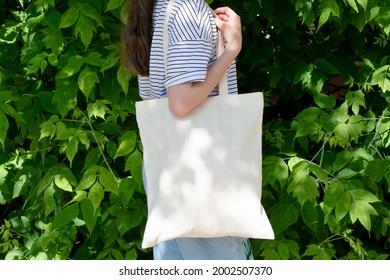 Empty reusable canvas tote bag mockup. Natural canvas eco-friendly shopper bag on girl's shoulder. Mockup for presentation of design or brand