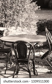 Empty riverside cafe at autumn. France. Round table and wicker chairs. Low season concept. Sepia photo.