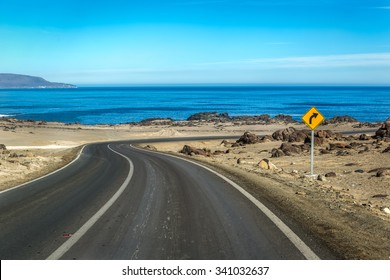 Empty road with a a blue sky and sea in the background. Chile, South America