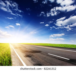 Empty road with cloudy sky and sunlight