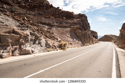 An empty road curving into the rocky hillside in a hot and arid landscape.