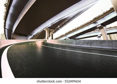 Empty road floor with city overpass viaduct bridge of neon lights night scene
