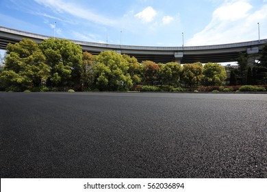 Empty road floor surface with city viaduct overpass bridge background
