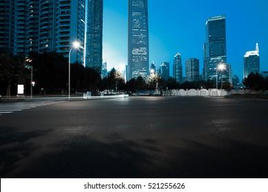 Empty road floor surface with modern city landmark buildings of night scene in Shanghai