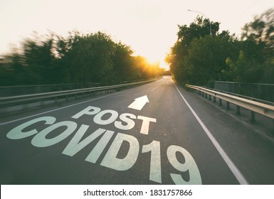 "The empty road in the forest and the text on the asphalt ""Post covid19""."