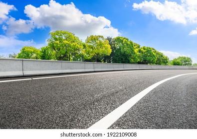 Leere Straße und grüner Baum unter blauem Himmel.
