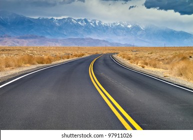 And empty road headed into Lone Pine, California.  The Eastern Sierra Mountains can be seen in the background with snow caps