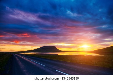 Empty road leading along the coast. Location place island Iceland, Europe. Typical Icelandic landscape. Popular tourist attraction. Dramatic evening, picturesque scene. Discover the beauty of earth.