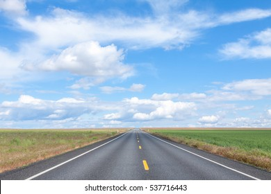 Empty road leading to horizon of blue sky and puffy white clouds, Palouse Region, Eastern Washington, U.S.A.