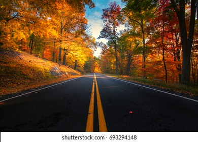 Empty road leading through fall foliage at Bear Mountain New York. During Peak Foliage season.