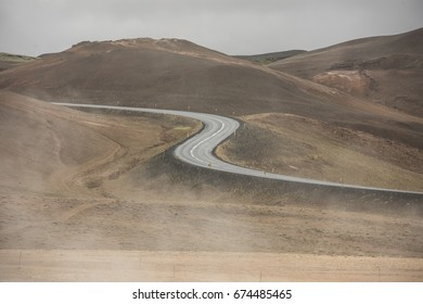 Empty Road leading through the mountain landscape looks like a big symmetric S letter, Iceland.